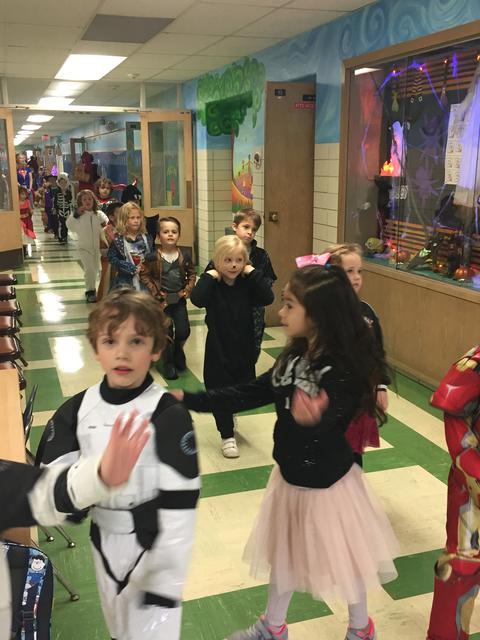 Kindergarten students walk through halls for parade