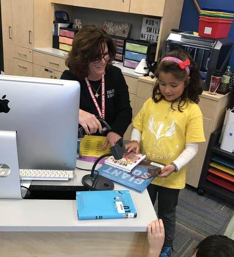 student and teacher looking at books