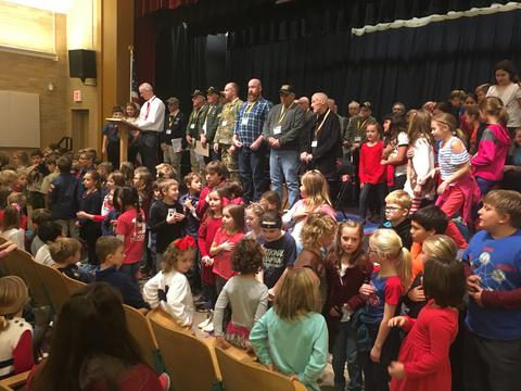 principal with veterans on stage