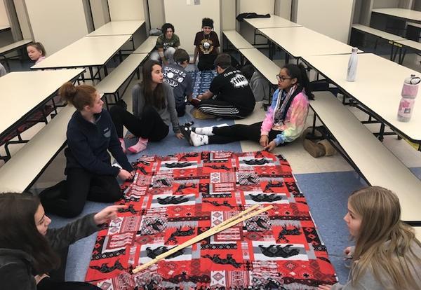 Students sitting on floor around blanket