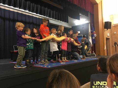 line of children holding a snake