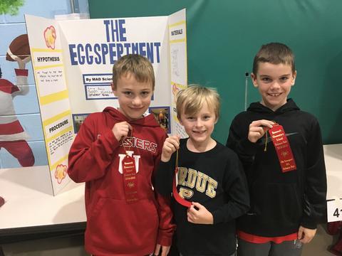 three boys holding ribbons
