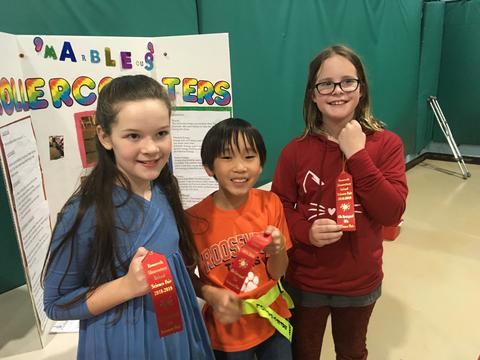 students displaying ribbons
