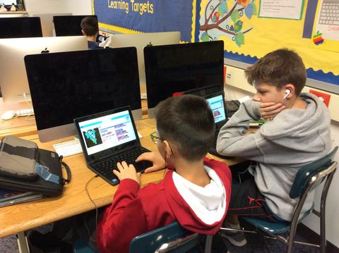 two boys collaborating on chromebooks