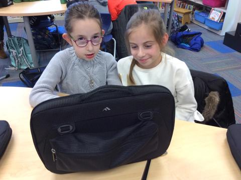 two girls working together on chromebook