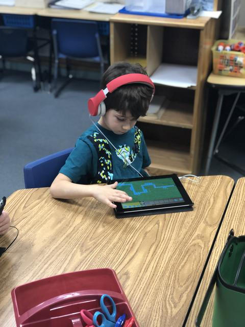 boy in headphones working on ipad