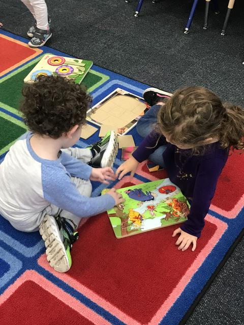students on a rug doing puzzles