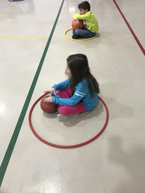 girl sitting on gym floor with hoola hoop and basketball