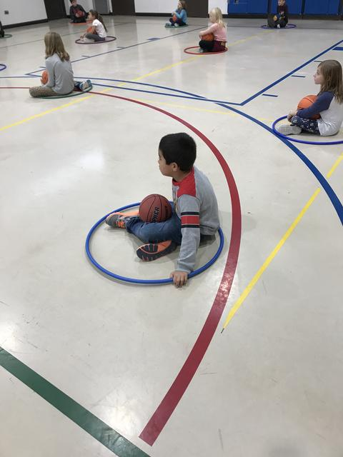 boy sitting on gym floor with hoola hoop and basketball