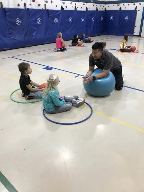 PE teacher on gym floor with students