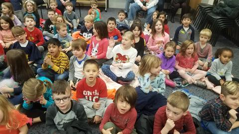 Kindergarteners sing along to holiday songs