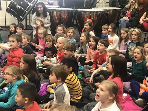 Kindergarten students sing along to holiday songs