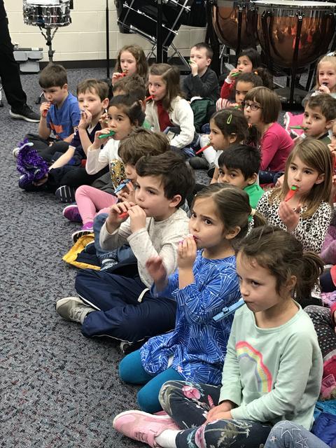 Kindergarten students practice the kazoo