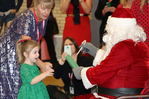 Three year old girl accepts present from Santa