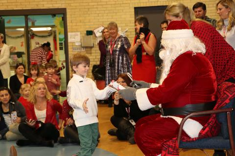 Three year old boy accepts present from Santa