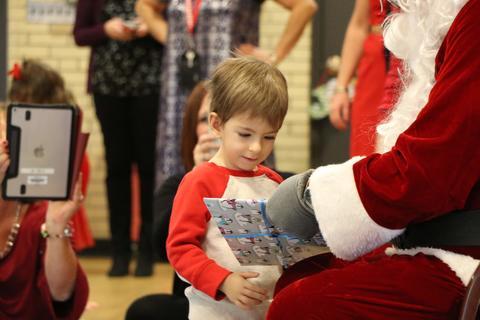 Three year old boy looks carefully at what Santa gives him