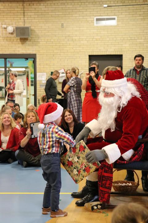 Boy with Santa hat accepts gift from Santa
