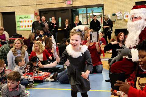 Girl excitedly accepts gift from Santa