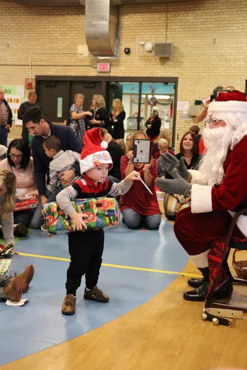 Boy with Santa hat gets gift from Santa