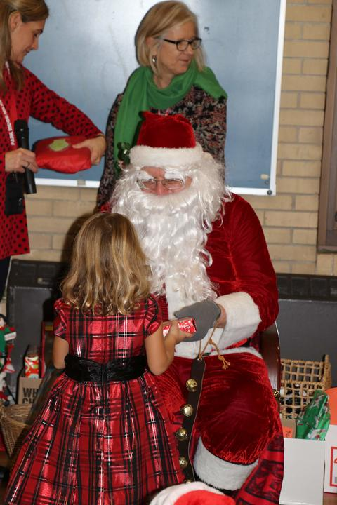 Girl in red dress gets gift from Santa