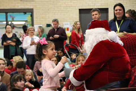 Four year old girl accepts gift from Santa