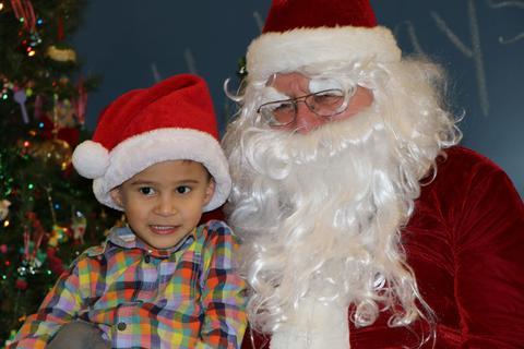 Boy in Santa hat sits on Santa's lap