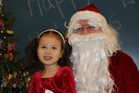 Girl in red holiday dress sits on Santa's lap