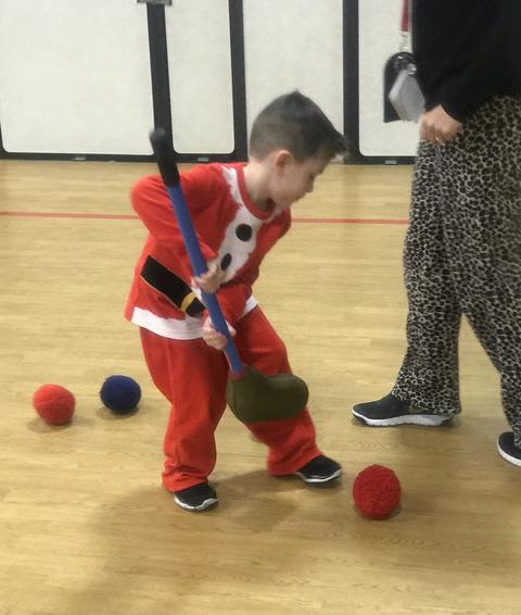 boy playing in gym dressed in santa outfit