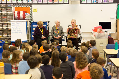 retired teachers presenting with a book