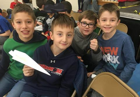 four students with paper airplanes