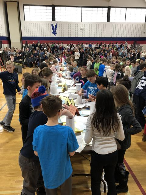 Large group of students creating egg drop containers