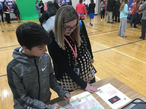 Student showing project to staff member