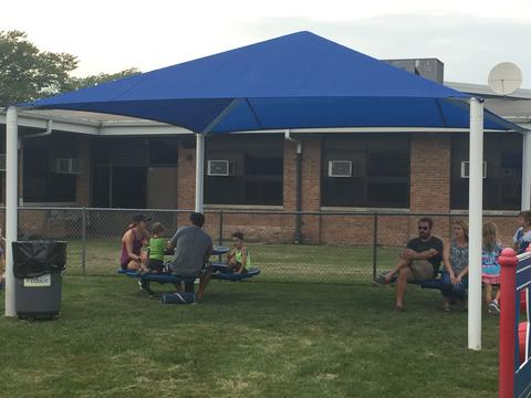 Families sit under our new sun shade