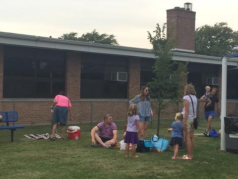 Families enjoy picnic on ground