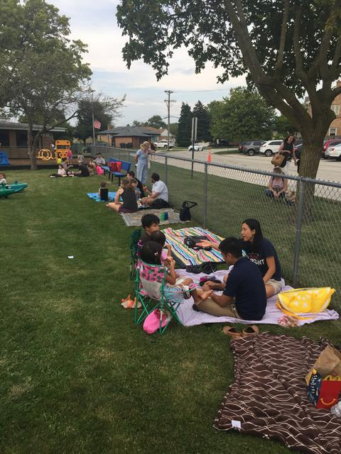 Families put blankets down for picnic dinner