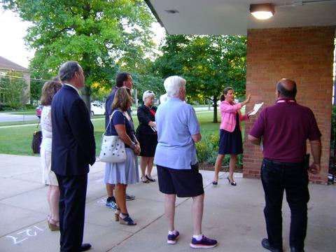 Dr. Heinz describes work to group at the entrance to Washington School