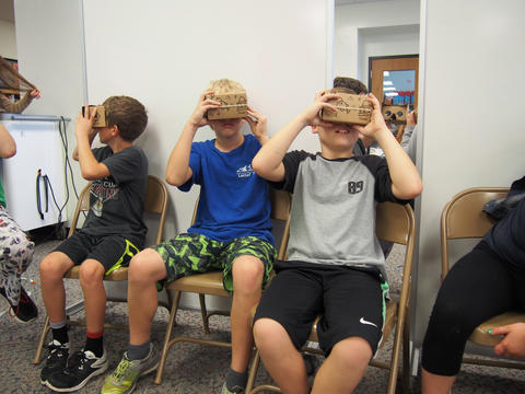 Three boys using virtual reality viewers