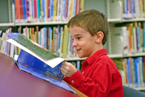 A child reading a book in the library.