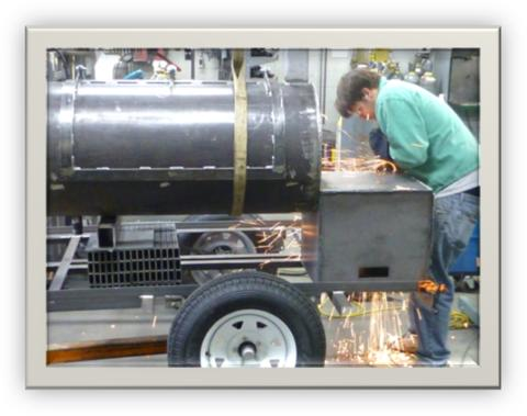 This is the initial fitting of the smoker to the trailer frame. The student is grinding the top of the fire box welds.