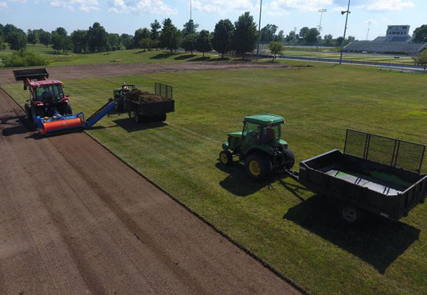 Tractors roll new sod over Rasmussen Soccer Field on the Lamoni campus