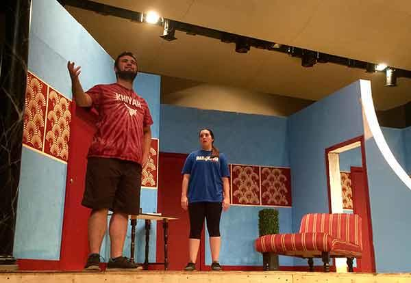 Male and female theatre students rehearsing on a dressed stage