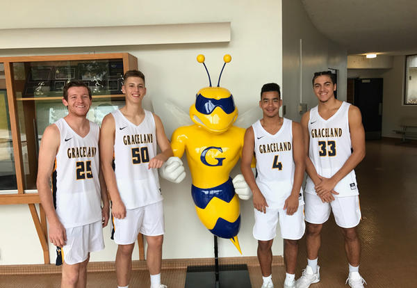 Men's basketball team members stand with new Sting Yellowjacket mascot statue