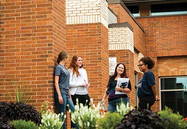Female students talk on the outside patio of the Independence Campus