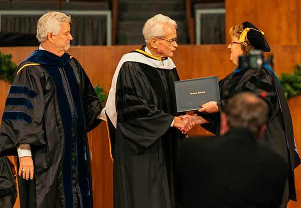 Pat Draves and Harry Ashenhurst present the Honorable Leonard L. Boswell with an honorary doctorate