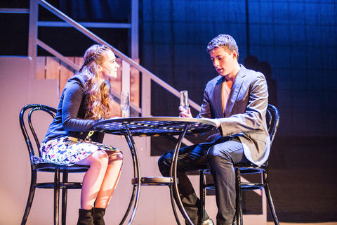 Male and female actor on-stage performing sitting at a bistro table