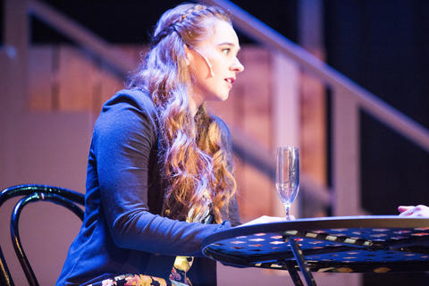 Female actor performing on-stage sitting at a bistro table.