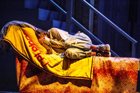 female actor performs on-stage lying in a bed.