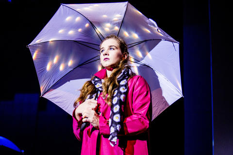 Close-up of female actress performing on-stage with an umbrella.