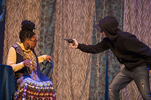 Male actor point gun at Haley Johnson's character on-stage in scene.