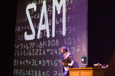 Male actor performing on-stage with the name SAM on a large screen behind him.